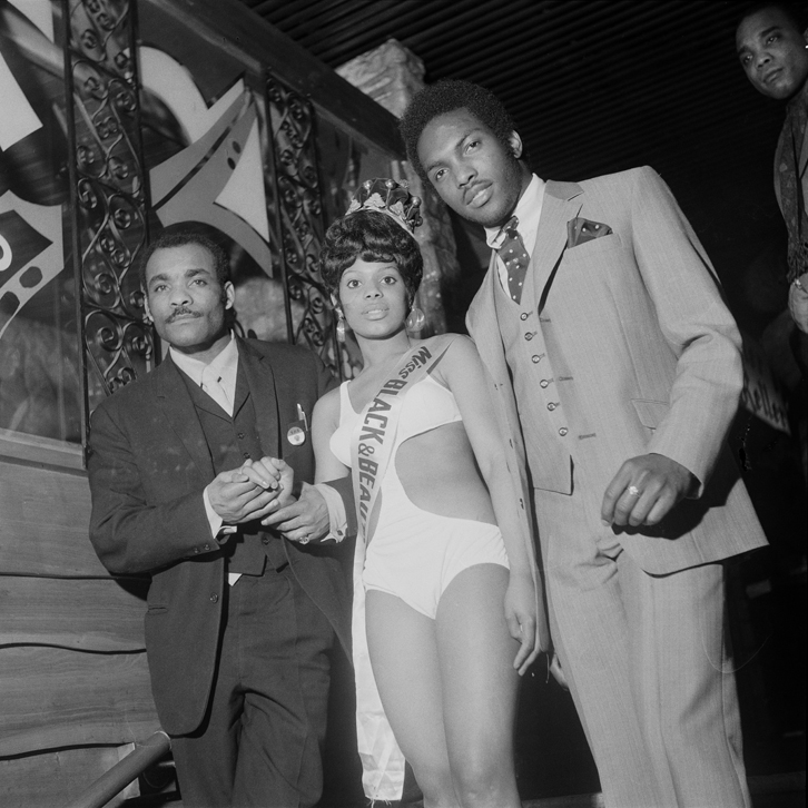 (unidentifed) Miss Black & Beautiful escorted by two men, Hammersmith Palais, London, 1970s.