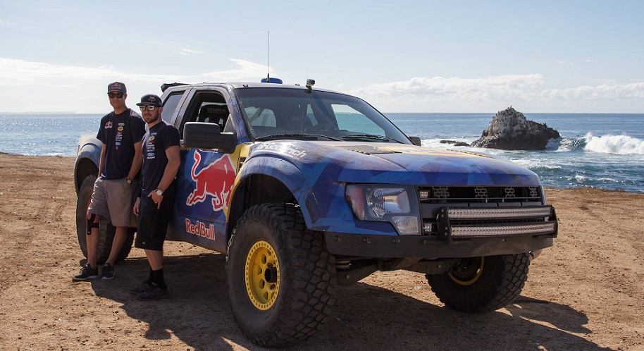 Pete Mortensen and Bryce Menzies pose for a photo while standing next to their Trophy Truck designed for the SCORE Baja 1000