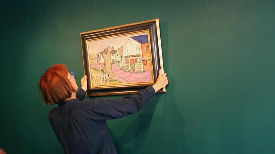 Jane Anderson hangs a painting by Edith, still from the film