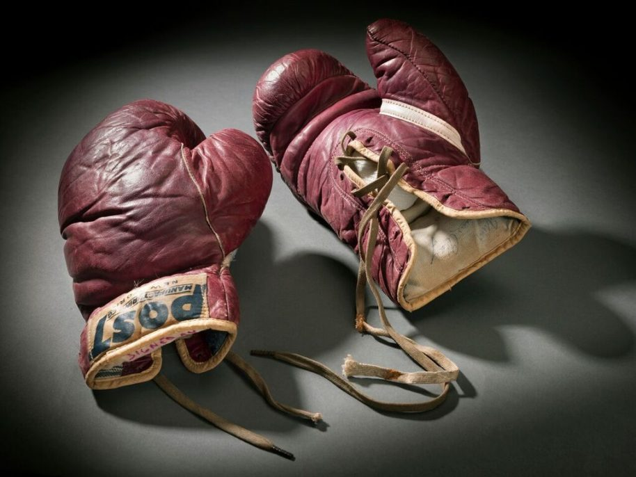 Created by: Post Manufacturing Co. Worn by: Muhammad Ali Training boxing gloves used and signed by Cassius Clay 1960 leather, cloth, thread a: 10 1/4 x 6 x 3 7/8 in. (26 x 15.2 x 9.8 cm) b: 10 1/4 x 5 5/8 x 4 in. (26 x 14.3 x 10.2 cm) Collection of the Smithsonian National Museum of African American History and Culture No Known Copyright Restrictions No Known Copyright Restrictions Collection of the Smithsonian National Museum of African American History and Culture