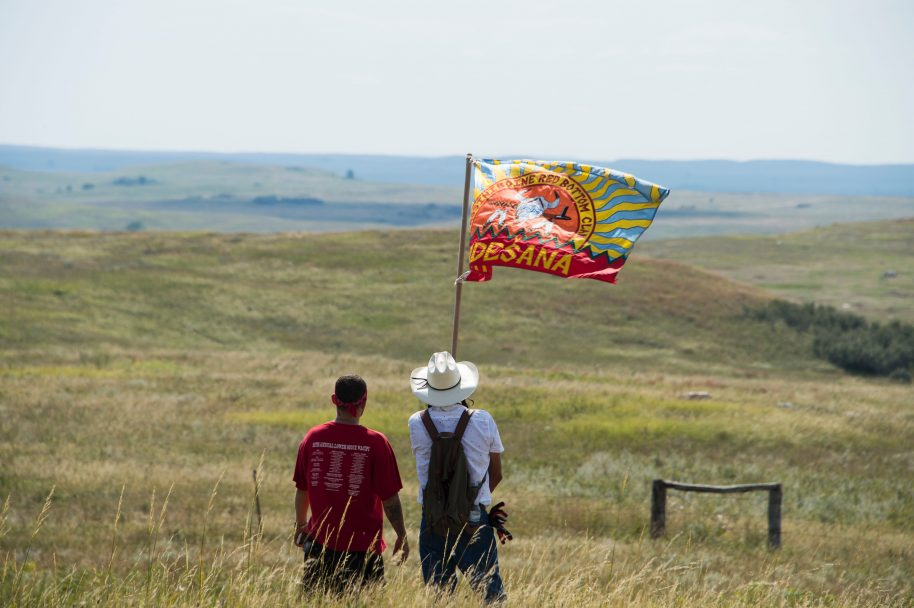 Native American protestors wave a clan flag over land designated for the Dakota Access Pipeline (DAPL), after protestors confronted contractors and private security guards working on the oil pipeline project, forcing them to retreat, September 3, 2016, near Cannon Ball, North Dakota. ROBYN BECK/AFP/Getty Images.