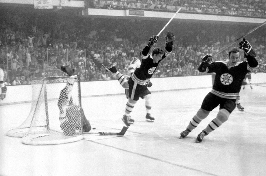 Bobby Orr #4 of the Boston Bruins flies through the air after sliding the puck past goalie Glenn Hall and tripped by Noel Picard of the St. Louis Blues as Orr scored the game winning overtime goal during Game 4 of the 1970 Stanley Cup Finals on May 10, 1970 at the Boston Garden in Boston, Massachusetts. The Bruins defeated the Blues 4-3 and won the series 4-0. (Photo by Bruce Bennett Studios/Getty Images)