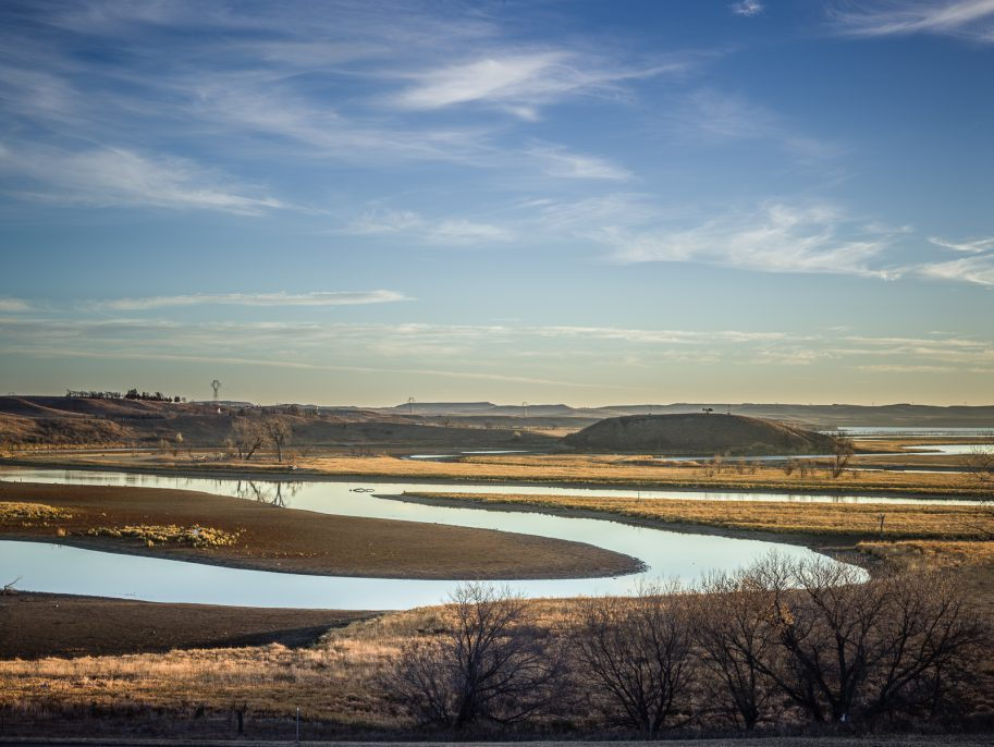 Taken from a bluff adjacent to the camp looking east toward the Missouri River, at the site where Dakota Access LLC awaits a permit to tunnel beneath. The large bluff on the right is a sacred site of the Standing Rock Tribe, and has been the location of frequent confrontations with riot police, as police presence on the hill is desecrates the site. Photo © Matt Hamon
